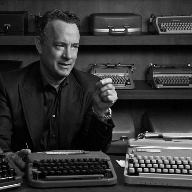 Photo of actor, Tom Hanks, with examples of typewriters from his collection
