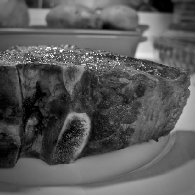 Black and white photo of a t-bone steak with soft-focus background